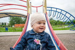 Little baby girl in jeans and a cap down from a hill on the playground with swings Stock Photo
