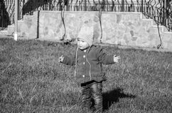 Little baby girl in jeans jacket and hat making learning to walk his first steps on the lawn in the green grass Stock Photo