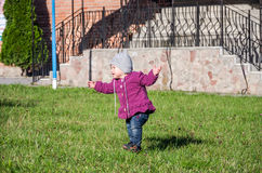 Little baby girl in jeans jacket and hat making learning to walk his first steps on the lawn in the green grass Stock Image