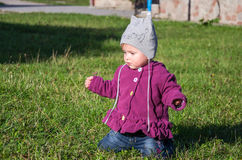 Little baby girl in jeans jacket and hat making learning to walk his first steps on the lawn in the green grass Stock Images
