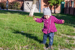 Little baby girl in jeans jacket and hat making learning to walk his first steps on the lawn in the green grass Royalty Free Stock Image