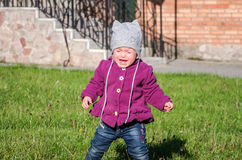 Little baby girl in jeans jacket and hat making learning to walk his first steps on the lawn in the green grass it has not very go Stock Photos