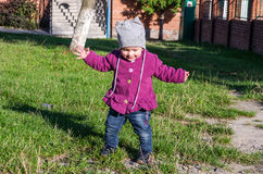 Little baby girl in jeans jacket and hat making learning to walk his first steps on the lawn in the green grass it has not very go Royalty Free Stock Photo