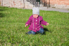 Little baby girl in jeans jacket and hat making learning to walk his first steps on the lawn in the green grass it has not very go Stock Images