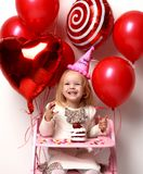 Little baby girl kid celebrate birthday with sweet cake and candies. On a light party background with red colorful balloons decorations royalty free stock photo