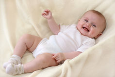 Little baby girl laughing. On blanket royalty free stock images