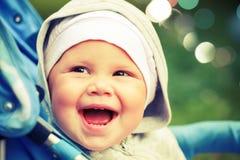 Little baby girl laughs in pram on the walk. Instagram toned effect stock image