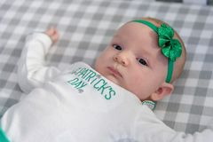 Little baby laying in crib wearing st patricks day outfit an hea. Little baby girl laying in bed with shamrock headband and blue eyes on st paddys day Royalty Free Stock Images