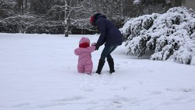 Little baby girl learn and her mom learn to walk on snow in winter day. 4K stock video