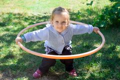 Little baby girl learns to deal with hulahup. The child holds the hoop with two hands. Baby is trying to twist the hoop around the waist. Girl dabbles with a royalty free stock image