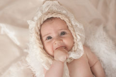 Little baby girl, lying on the bed, sucking her thumb stock images