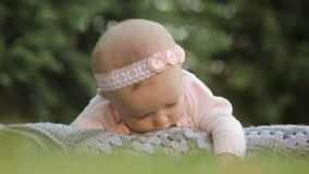 Little baby girl lying on the plaid in the summer park stock footage