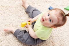 Little baby girl in middle of toys Stock Photos