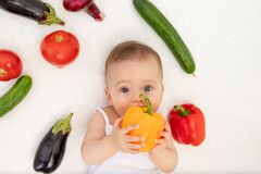 Little baby girl 6 months old sitting on the bed in the nursery with vegetables, baby`s first feeding, baby food concept, place