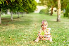 Little baby girl 7 months old sitting on a green lawn in a yellow dress and playing with a toy, walking in the fresh air, space