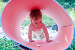 Little baby girl on nature on the lake made of karemat pipe and plays with her climb inside Stock Image
