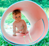 Little baby girl on nature on the lake made of karemat pipe and plays with her climb inside Royalty Free Stock Image