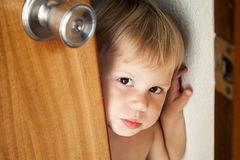 Little baby girl opens door and looks outside Royalty Free Stock Photography