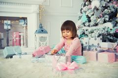 Little baby girl opens New Year gift near Christmas tree.  Royalty Free Stock Photography