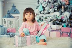 Little baby girl opens New Year gift near Christmas tree.  Stock Images