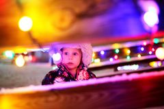 Little baby girl outside looking at Christmas Lights. A 1 year old baby girl is standing outside in her winter coat, looking at Christmas Lights at the Park royalty free stock photo