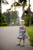 Little baby girl on the park alley stock images