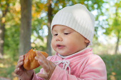 Little baby girl in park eats small pie Royalty Free Stock Image