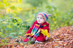 Little baby girl in park with golden maple leaves Royalty Free Stock Photos