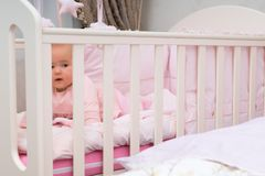 Little Baby Girl Peering Through Her Cot. Royalty Free Stock Photos