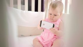 Little baby girl with phone in crib. Infant watching cartoon on mobile phone. Cute toddler looking smartphone in bed. Child with phone in cot stock footage