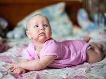 A little baby girl in pink clithes lying at home on the bed royalty free stock image
