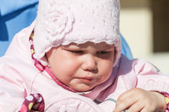 Little baby girl in pink crying, outdoor portrait Stock Photos