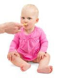 Little baby girl in pink dress eats from spoon Stock Images