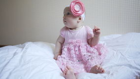 Little baby girl in pink dress is sitting on the bed in the bedroom stock video