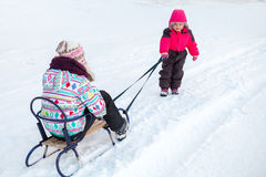 Little baby girl in pink pulling a sled with sister Royalty Free Stock Images