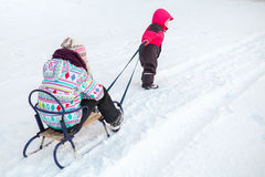 Little baby girl in pink pulling a sled with sister Royalty Free Stock Photography