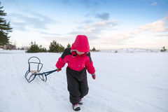 Little baby girl in pink pulling a sled Stock Photo