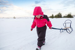 Little baby girl in pink pulling a sled Royalty Free Stock Photos