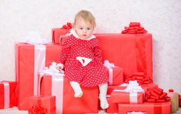 Little baby girl play near pile of gift boxes. Gifts for child first christmas. Celebrate first christmas. Baby first. Christmas once in lifetime event. Sharing stock photos