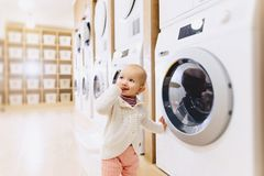 little baby girl looking at a washing machine Royalty Free Stock Photography