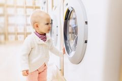 little baby girl looking at a washing machine Stock Photos