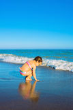 Little baby girl playing on the beach alone. Stock Images