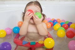 Little baby girl playing with colored balls Royalty Free Stock Images