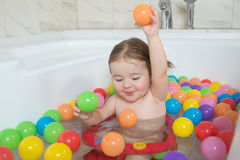 Little baby girl playing with colored balls Stock Photo