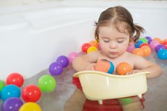Little baby girl playing with colored balls Stock Image