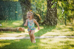 The little baby girl playing with garden sprinkler. Summer outdoor water fun and green grass royalty free stock images