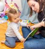 Baby Girl. Reading. Joy. Book. Mother stock images