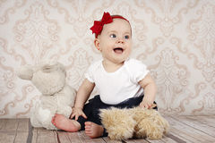 Little baby girl playing with plush toys stock photos