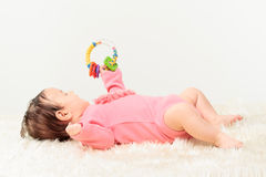 Little baby girl playing with rattle Stock Photos