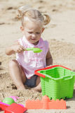 Little baby girl playing sand toys at the beach Stock Image